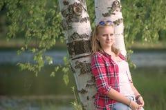 Retrato de una mujer joven hermosa que descansa cerca del leanin del lago Foto de archivo
