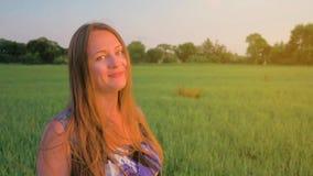 Retrato de una mujer joven hermosa que se coloca en un campo verde en la puesta del sol, sonriendo y relajándose en naturaleza Re almacen de video