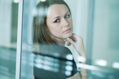 Mujer triste en la ventana Fotos de archivo