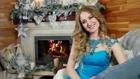 Retrato de una mujer joven, muchacha hermosa que se sienta por la chimenea en la cual el fuego está quemando en la atmósfera case almacen de metraje de vídeo
