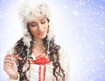 Retrato de una mujer joven que abre un regalo de Navidad Imagen de archivo libre de regalías