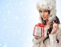 Retrato de una mujer joven que abre un regalo de Navidad Fotos de archivo libres de regalías