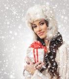 Retrato de una mujer joven que abre un regalo de Navidad Imagen de archivo