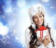 Retrato de una mujer joven que abre un regalo de Navidad Fotografía de archivo