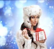 Retrato de una mujer joven que abre un regalo de Navidad Imagenes de archivo