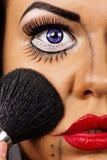 Retrato de una mujer joven que aplica el cosmético Imagen de archivo libre de regalías