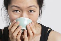 Retrato de una mujer joven que bebe del cuenco sobre fondo gris claro Imagen de archivo