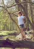 Retrato de una mujer joven que camina sobre tronco de árbol foto de archivo