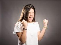 Retrato de una mujer joven que celebra siendo un ganador imagen de archivo