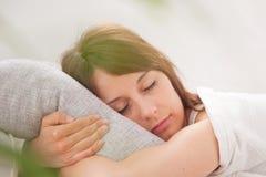 Retrato de una mujer joven que duerme en la cama Imagen de archivo