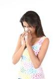 Retrato de una mujer joven que estornuda Imagen de archivo