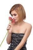 Retrato de una mujer joven que huele una flor Imágenes de archivo libres de regalías