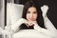 Retrato de una mujer joven que miente en cama en la ventana Fotografía de archivo