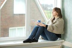 Mujer joven que mira hacia fuera la ventana Fotografía de archivo