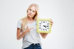 Retrato de una mujer joven que señala el finger en el reloj de pared Foto de archivo libre de regalías