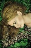 Retrato de una mujer joven que se relaja en hierba Imágenes de archivo libres de regalías