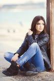 Retrato de una mujer joven que se sienta en la acera Fotografía de archivo