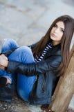 Retrato de una mujer joven que se sienta en la acera Imagen de archivo libre de regalías