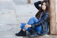 Retrato de una mujer joven que se sienta en la acera Foto de archivo libre de regalías