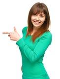 Retrato de una mujer joven que señala a la izquierda Imagen de archivo