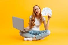 Retrato de una mujer joven, sentándose en el piso, usando un ordenador portátil portátil y sosteniendo el dinero en su mano, en u foto de archivo