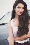 Retrato de una mujer joven sonriente con el coche en fondo foto de archivo libre de regalías