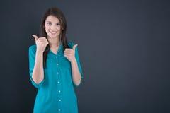 Retrato de una mujer joven sonriente con los pulgares para arriba en escuela Foto de archivo