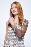 Retrato de una mujer joven sonriente del jengibre que muestra el tatuaje en el h Imagenes de archivo