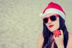 Retrato de una mujer joven sonriente en el sombrero y el sungla de Santa Claus Imagen de archivo libre de regalías