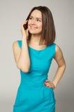 Retrato de una mujer joven sonriente que habla en el teléfono móvil Fotografía de archivo libre de regalías
