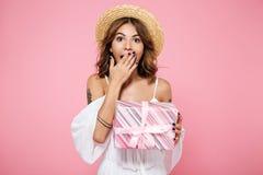 Retrato de una mujer joven sorprendida en el sombrero de paja que lleva a cabo el presente Imagen de archivo libre de regalías