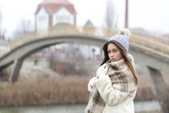 Retrato de una mujer joven y hermosa en un abrigo de pieles con el casquillo a Imágenes de archivo libres de regalías