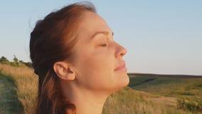 Retrato de una mujer, mujer de la forma de vida por la tarde en el primer del campo, el concepto de una forma de vida sana y almacen de metraje de vídeo
