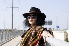 Retrato de una mujer de la moda en estilo del vaquero en el puente Fotografía de archivo libre de regalías