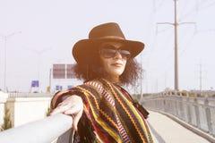Retrato de una mujer de la moda en estilo del vaquero en el puente Foto de archivo libre de regalías