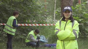Retrato de una mujer de la policía en uniforme del verde en el fondo del incidente en el parque, mirando la cámara almacen de video