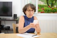 Retrato de una mujer madura con un teléfono Foto de archivo libre de regalías
