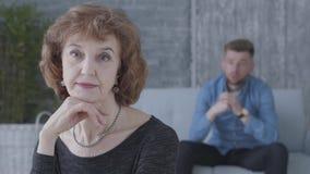 Retrato de una mujer madura mayor que mira en la c?mara en el primero plano La figura borrosa del hombre infeliz triste almacen de metraje de vídeo