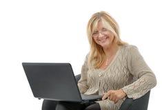 Retrato de una mujer madura sonriente que usa el ordenador portátil fotos de archivo