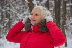 Retrato de una mujer mayor agradable en la madera de la nieve del invierno en capa roja Imagen de archivo