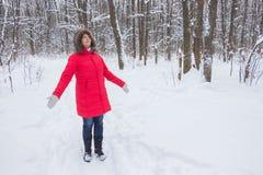 Retrato de una mujer mayor agradable en la madera de la nieve del invierno en capa roja Fotografía de archivo