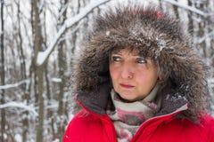 Retrato de una mujer mayor agradable en la madera de la nieve del invierno en capa roja Imagen de archivo libre de regalías