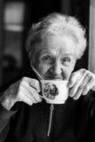 Retrato de una mujer mayor con una taza de té en sus manos Imagen de archivo