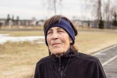 Retrato de una mujer mayor feliz que presenta en la naturaleza en auriculares fotografía de archivo