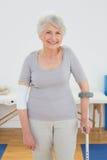 Retrato de una mujer mayor sonriente con la muleta Foto de archivo libre de regalías