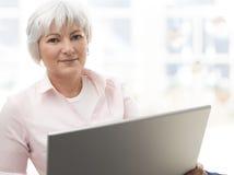 Mujer mayor sonriente que trabaja en el ordenador portátil Imagen de archivo