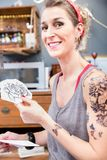 Retrato de una mujer de moda feliz para elegir dos rosas para su nuevo tatuaje Imagenes de archivo