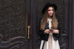 Retrato de una mujer morena de moda con la mirada fresca que celebra el teléfono móvil mientras que se opone en la calle a puerta Fotos de archivo libres de regalías