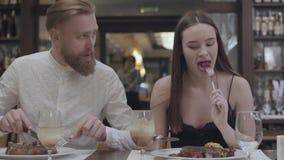 Retrato de una mujer morena linda joven y de un hombre barbudo que cenan o cena en un restaurante o un café almacen de video