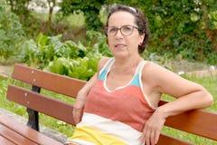 Retrato de una mujer morena de mediana edad con las lentes, outdoo imagen de archivo libre de regalías